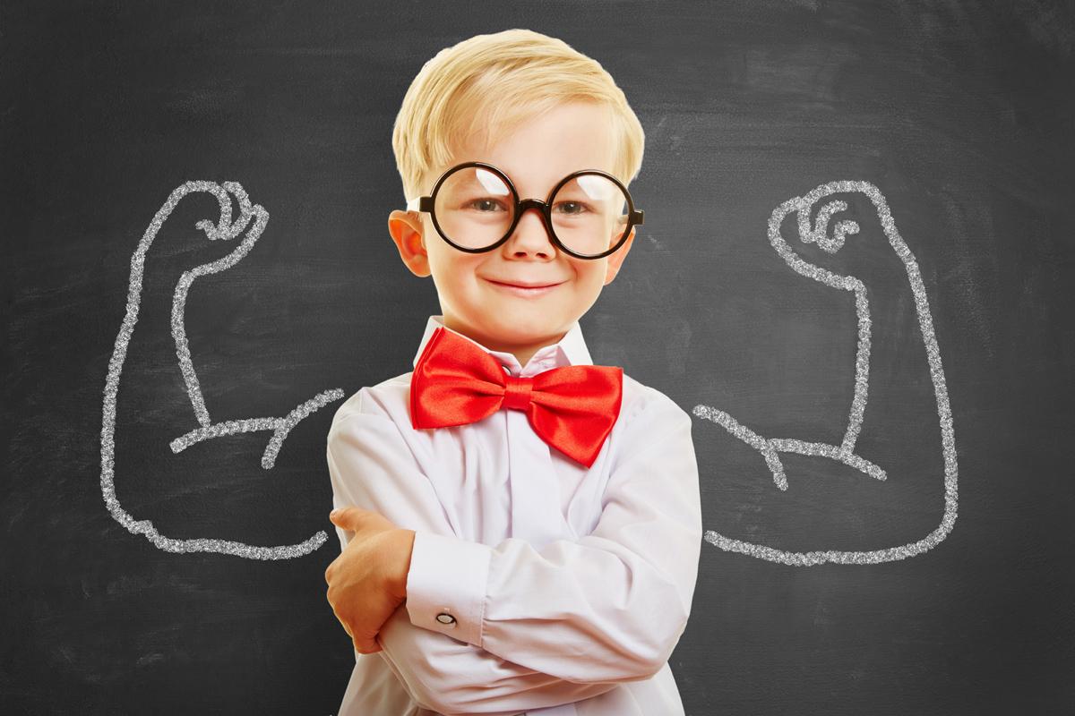 Lächelndes Kind steht vor Tafel mit Muskeln aus Kreide